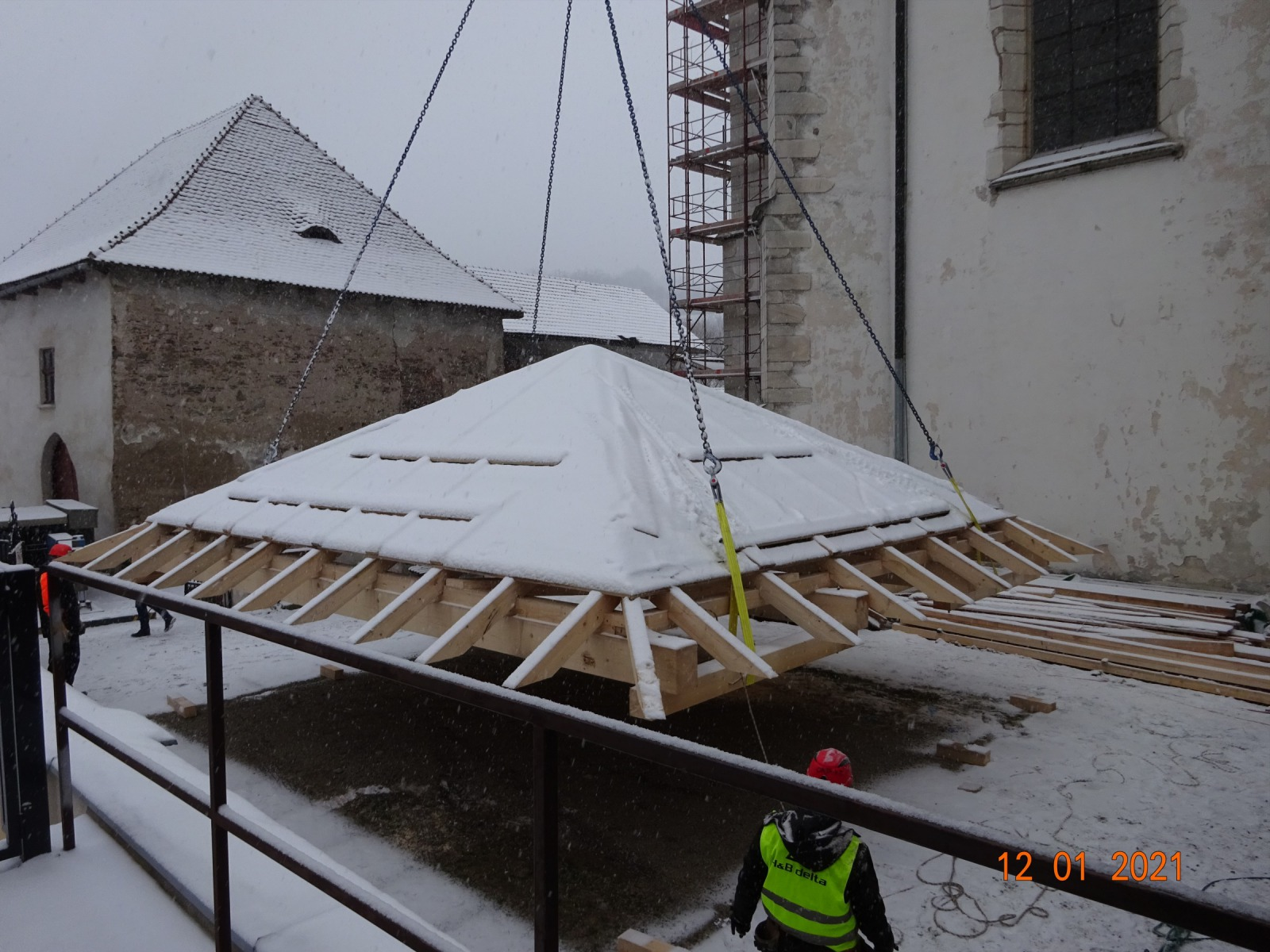 Zvedání dočasné střechy věže pro usazení na věž.