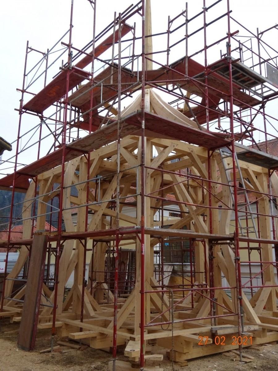 Stavba krovu nové střechy věže osazené ramenáty tvořící tvar kopule.