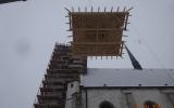 Dočasnou střechu věže zvedá jeřáb na věž.